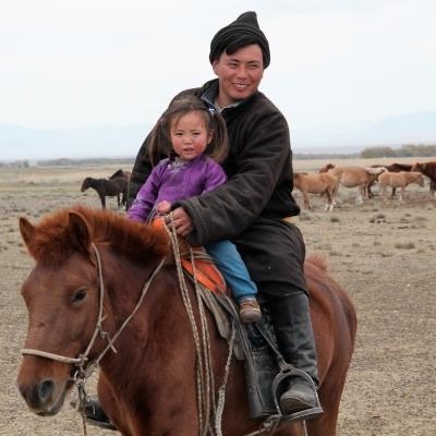 A father and daughter ride a horse at our Nomad Project for volunteers in Mongolia.